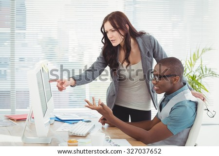 Business people gesturing while looking at computer in office - stock photo