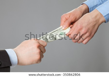Business people hands pulling money, closeup shot on grey background