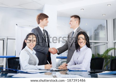 Business people handshake, businessmen hand shake on background, during meeting after signing agreement in office, businesswoman at desk smile - stock photo