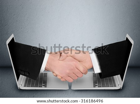 Business people handshake through computer - stock photo