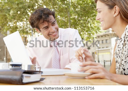 Business people having a coffee in a coffee shop terrace, having a meeting and using a laptop computer. - stock photo
