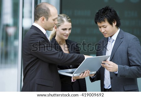 Business People having a meeting with computer outside