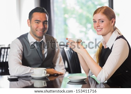 Business people having coffee and looking at camera in a cafe