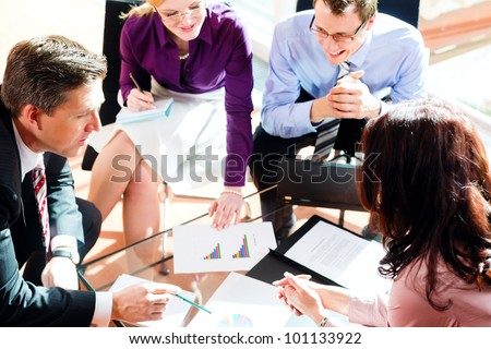 Business people having meeting or workshop in office checking profit growth graph and documents - stock photo