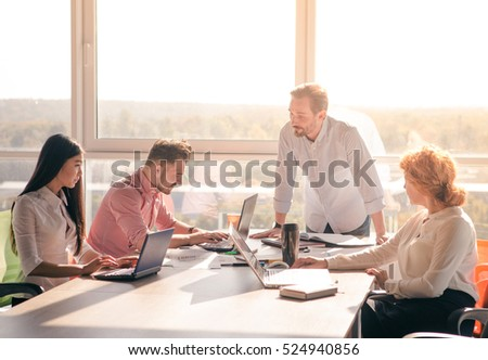 Business people having round table in board room in office. Group of people discussing business projects and strategies while sitting at table.