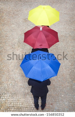 Business people hidden under colorful umbrellas, lined up - stock photo