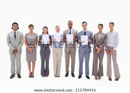 Business people holding four white supports for letters against white background - stock photo