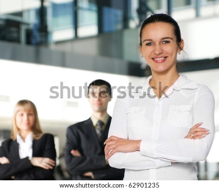 Business people in office (WARNING! Focus only on the lady in front of image) - stock photo