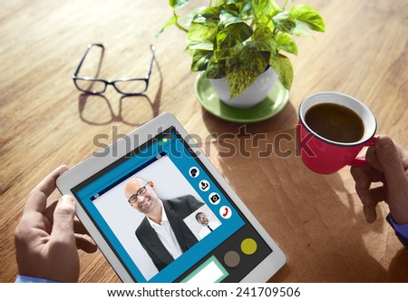 Business People in Video Conference at Table - stock photo