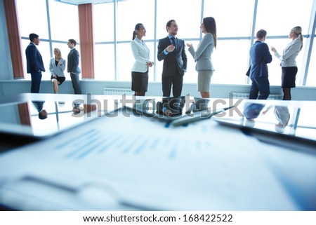 Business people interacting in office with workplace in front of them - stock photo