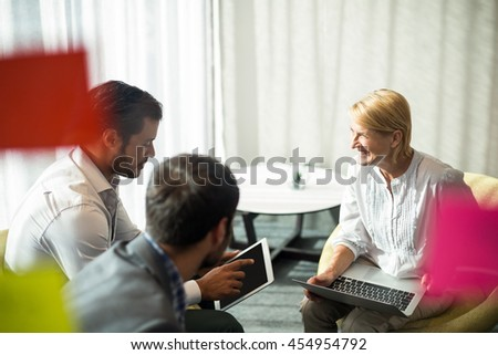 Business people interacting using digital tablet and laptop in the office