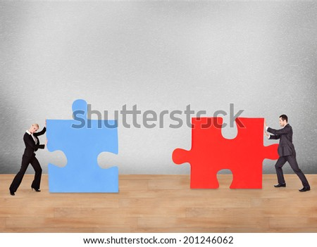 Business people joining puzzle pieces on desk - stock photo