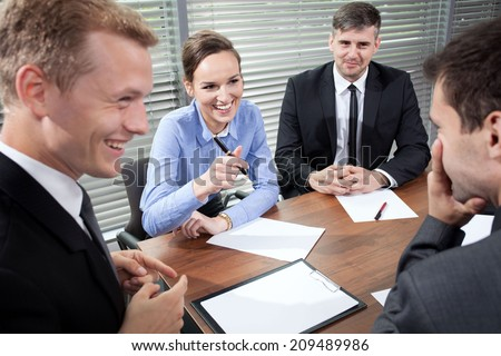 Business people laughing during business meeting, horizontal - stock photo