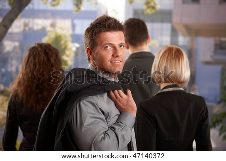 Business people leaving office at afternoon mid-adult businessman looking back, smiling. - stock photo