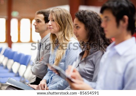 Business people listening and taking notes during a presentation - stock photo