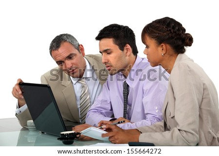 Business people looking at a laptop - stock photo