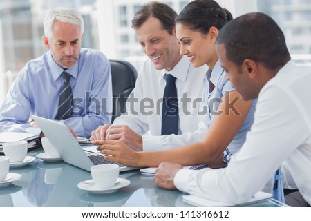 Business people looking at a laptop during a meeting - stock photo
