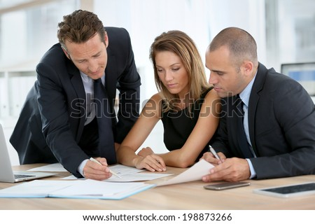 Business people looking at budget forecast - stock photo