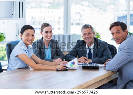 Business people looking at camera during meeting in office - stock photo
