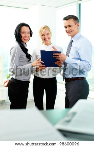 Business people looking at camera while discussing plan - stock photo