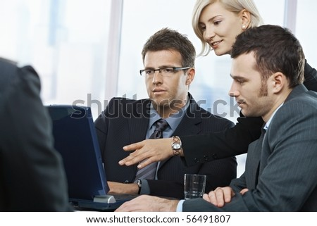 Business people looking at laptop, talking at meeting table in office,
