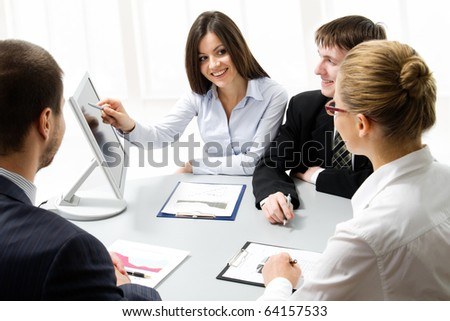 Business people looking at monitir, talking at meeting table in office - stock photo