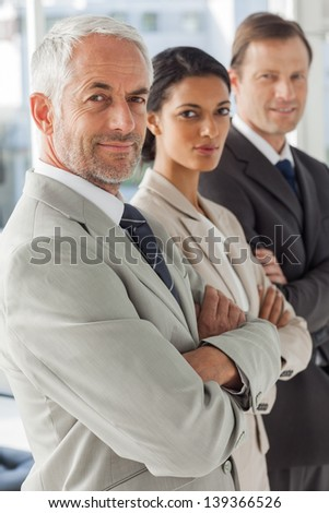 Business people looking in the same way with their arms crossed - stock photo
