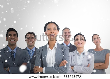 Business people looking up in office against snow - stock photo