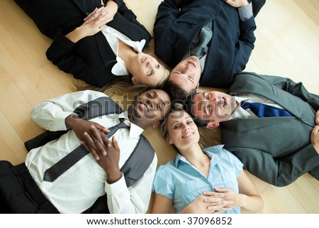 Business people lying in a circle on the floor of the office