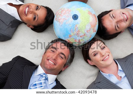Business people lying on the floor around a terrestrial globe smiling at the camera - stock photo