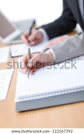 Business people making notes in notebooks sitting at the table. Close up of hands