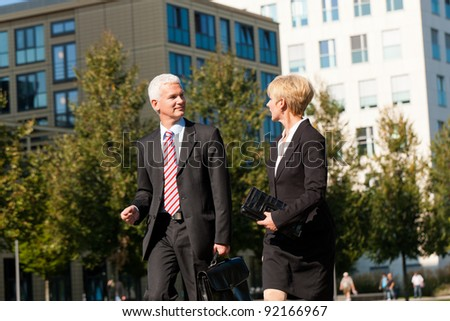 Business people - mature or senior -  talking outdoors and walking in a park - stock photo