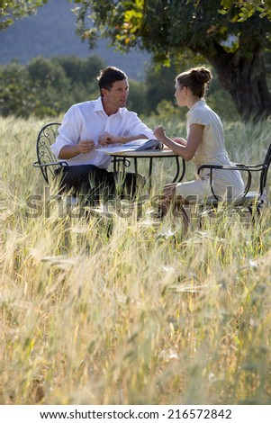 Business people meeting at table in rural field - stock photo
