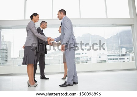 Business people meeting in bright office shaking hands