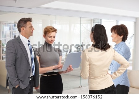 Business people meeting in office lobby talking working together.