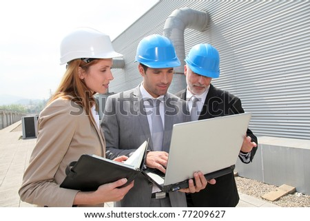 Business people meeting on industrial site - stock photo