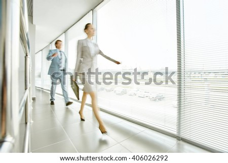 Business people moving along office corridor, blurred motion - stock photo