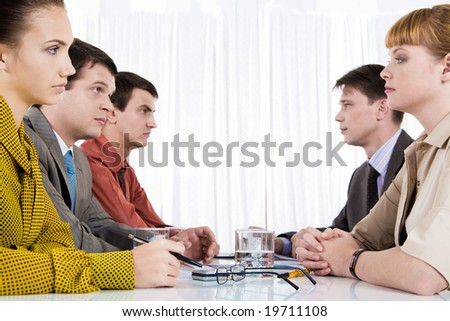 Business people of two opposite rows staring at each other seriously - stock photo