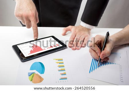 Business people on a meeting analyzing financial reports discussing the charts and graphs showing the results of their successful teamwork  - stock photo