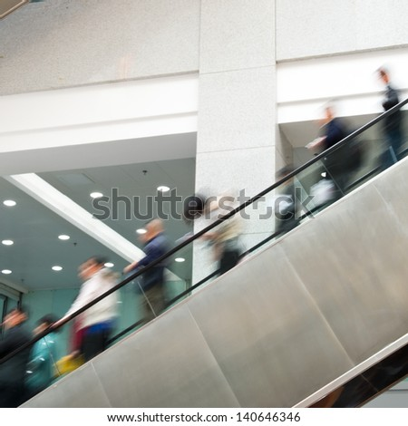 Business people on escalator.Blurred motion  - stock photo