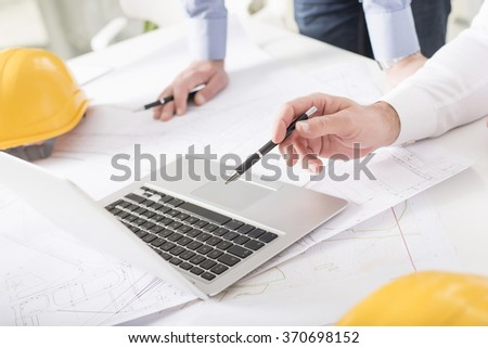 Business people on meeting in bright modern office with blueprint at desk check documents and business workflow on laptop - stock photo