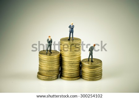 Business people on pile of coins. Business competition concept. Macro photo - stock photo