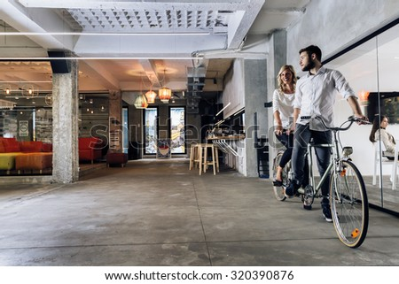 Business people on twin bicycle with mutual goals and same vision in business - stock photo