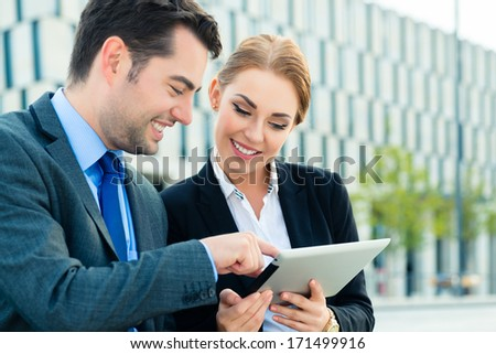 Business people or businessman and businesswoman working outdoor, using pad or tablet computer - stock photo