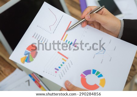 Business people pointing at business document during meeting - stock photo