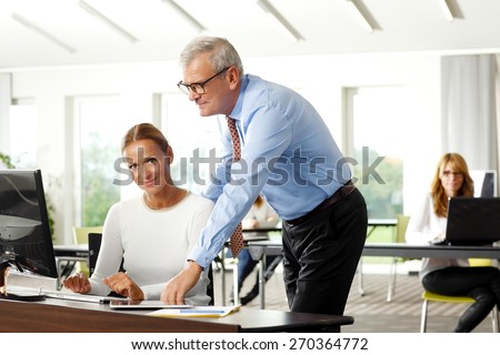 Business people portrait. Middle age businesswoman and senior businessman consulting while sitting at office in front of laptop. Businesswoman looking at camera and smiling.