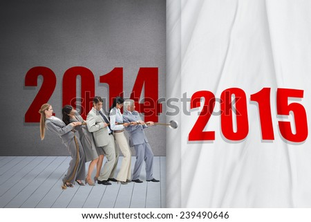 Business people pulling a rope against grey room - stock photo