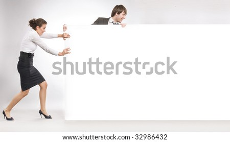 Business people pushing big white board, lots of copyspace - stock photo