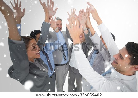 Business people raising their arms against snow