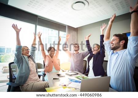Business people raising their arms during meeting in the office - stock photo